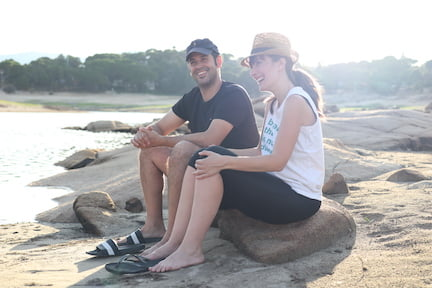 AF-sentados-roca-rio-foto-medio-lateral-plano-cercano-sonrien-miran-horizonte-super